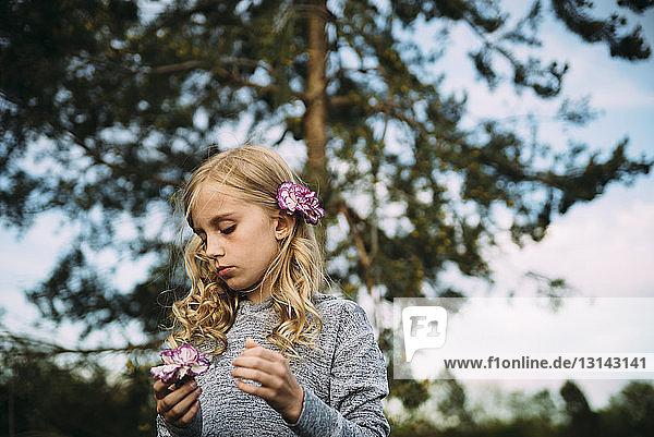 Mädchen mit Blumen an Bäumen stehend
