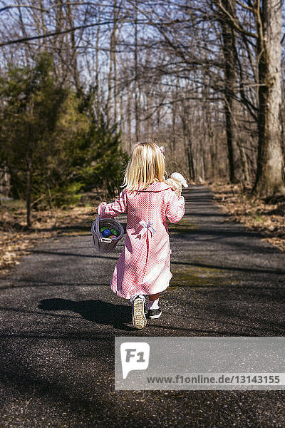 Rear view of girl with Easter eggs and stuffed toy walking on road amidst trees