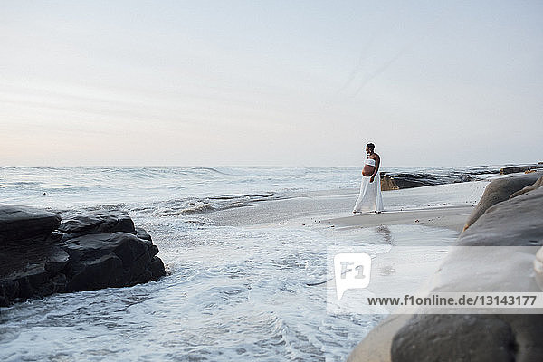 Pregnant woman walking at beach against sky during sunset