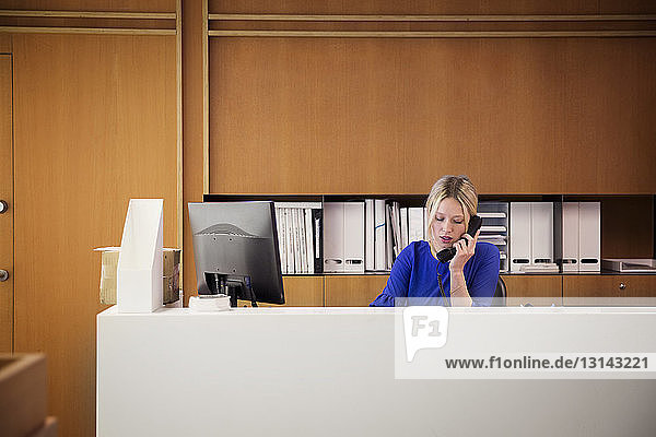 Geschäftsfrau telefoniert am Schreibtisch im Büro
