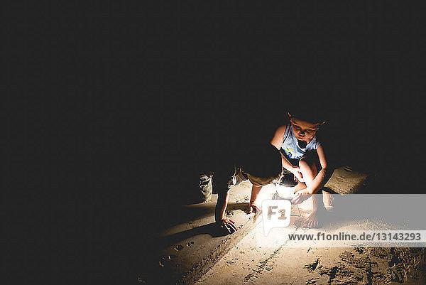 Hochwinkelansicht von Brüdern mit beleuchteten Beleuchtungsgeräten  die nachts im Freien spielen