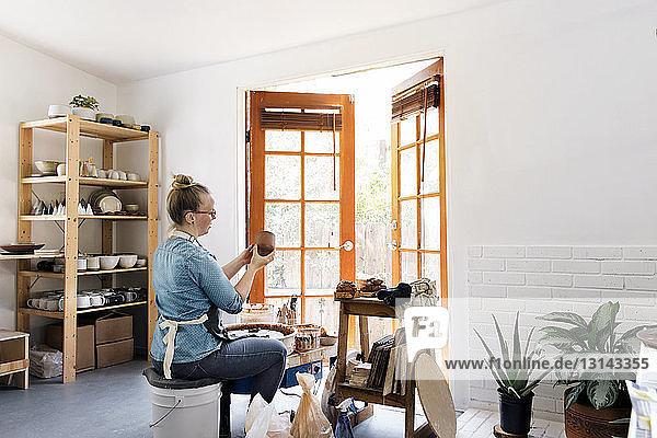 Frau hält Steingut bei Workshop