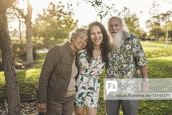 Portrait of smiling daughter with parents standing at park