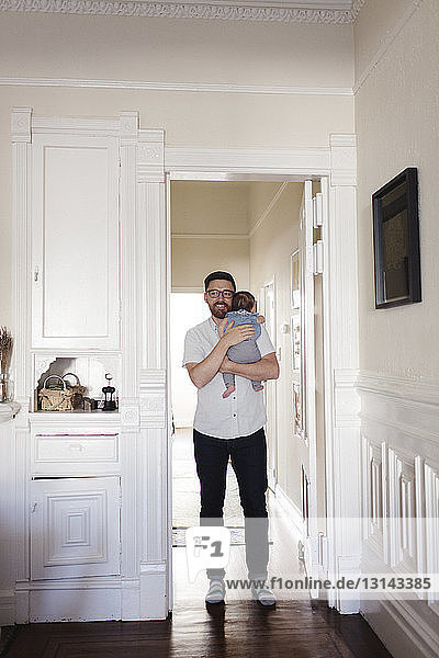 Father carrying daughter while walking in hallway at home