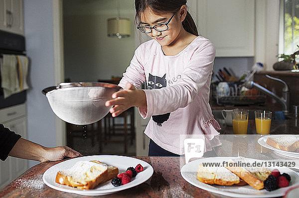 Mädchen streut Puderzucker auf Brot mit der Mutter in der Küche