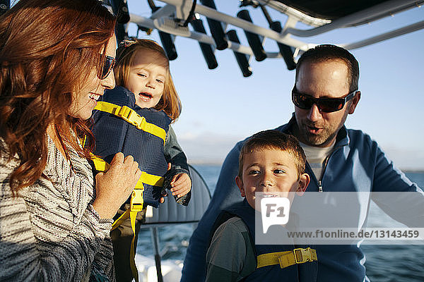 Children traveling with parents in boat on sunny day