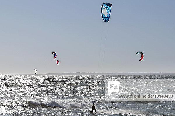Rückansicht eines Mannes beim Kitesurfen auf dem Meer gegen den Himmel