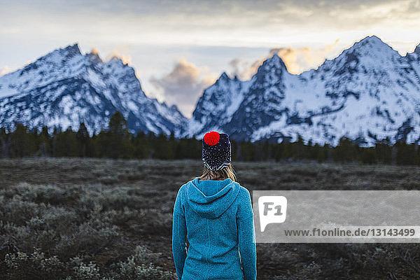 Frau  die im Winter auf dem Feld vor den Bergen steht und auf die Aussicht schaut