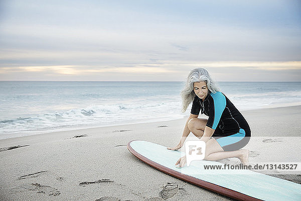 Female surfer cleaning surfboard at Delray beach during sunset