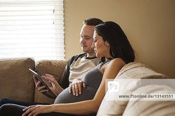 Mann benutzt Tablet-Computer  während schwangere Frau zu Hause auf dem Sofa sitzt