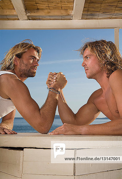young men arm wrestle at beach young men arm wrestle at beach