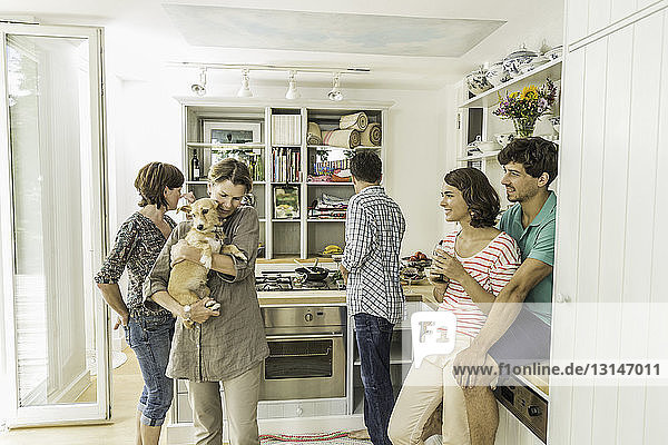 Five adult friends and dog gathering in kitchen