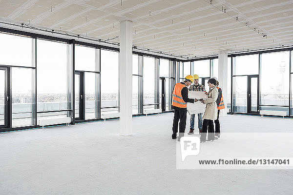 Group of people in empty office building with blueprint