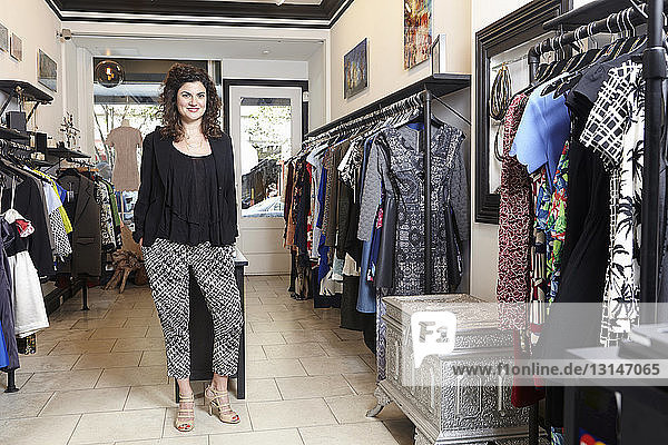 Portrait of mature woman standing in fashion boutique