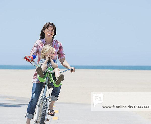 Woman and son cycling on beach  Venice  California  USA