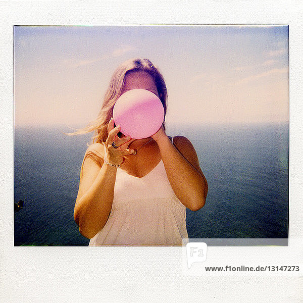 Instant film photograph of woman blowing up balloon