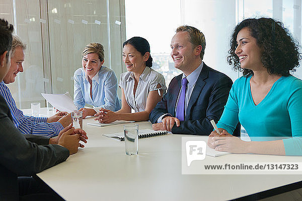 Office workers smiling in meeting in office