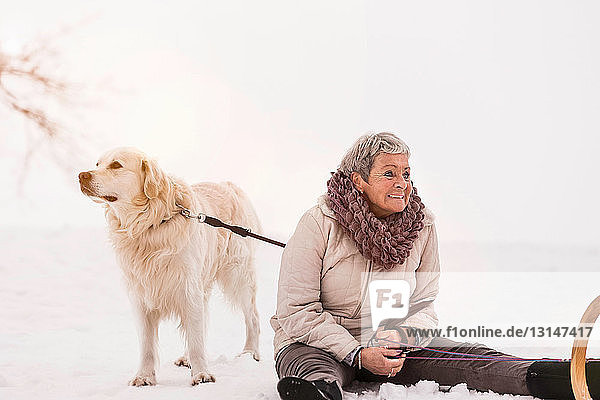 Woman sitting on snow with dog