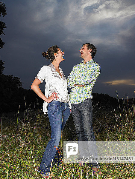 Man and woman in a field  laughing