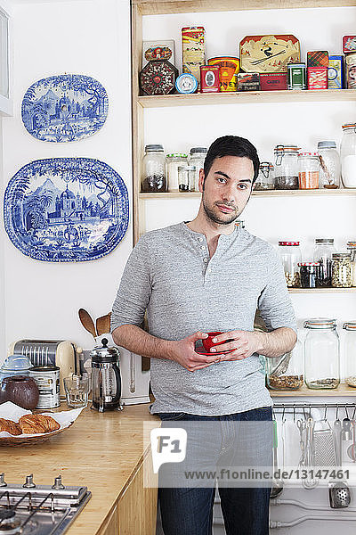 Mid adult man standing in kitchen holding coffee cup