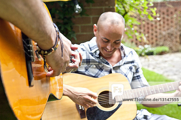 Cropped shot of two male friends playing acoustic guitar in garden