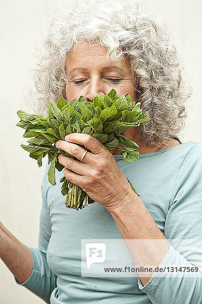 Mature woman smelling bunch of mint in garden