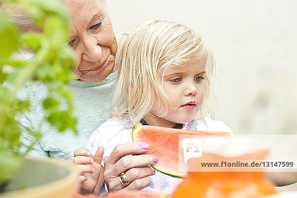 Senior woman and toddler great granddaughter eating melon slice at garden table