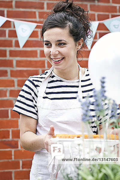 Young woman with fruit flan at garden party