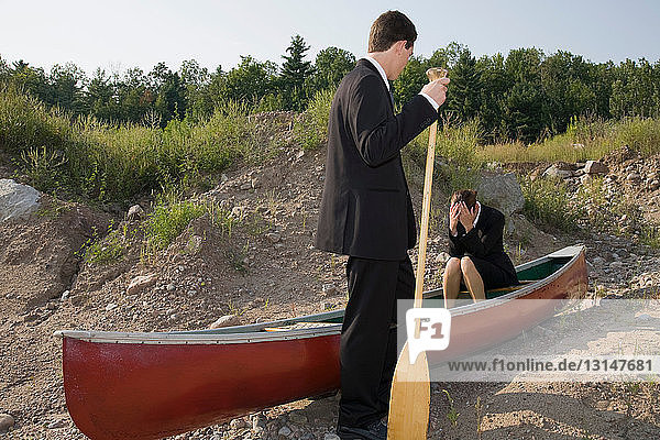 Business people in stranded canoe
