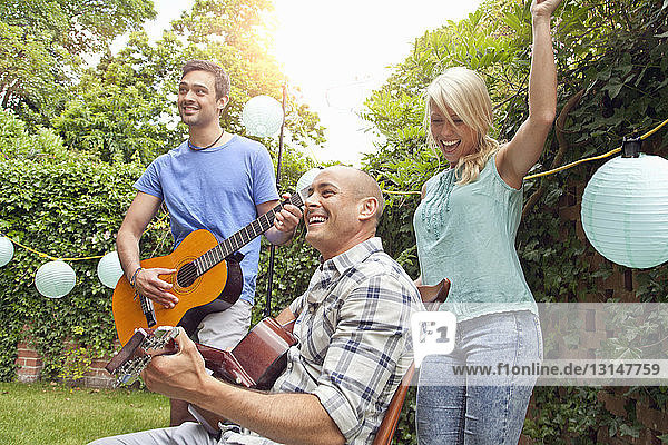 Male friends playing acoustic guitar in garden and young woman dancing