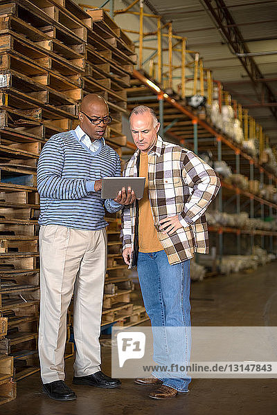Male warehouse worker using digital tablet  pallets in background
