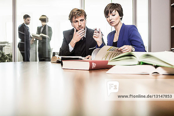 Lawyer and client with books in office