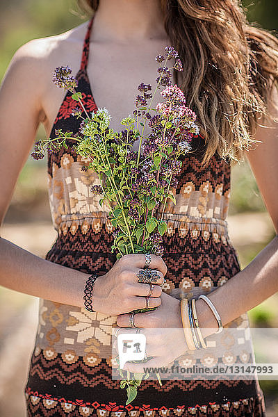 Cropped shot of young woman holding bunch of wildflowers