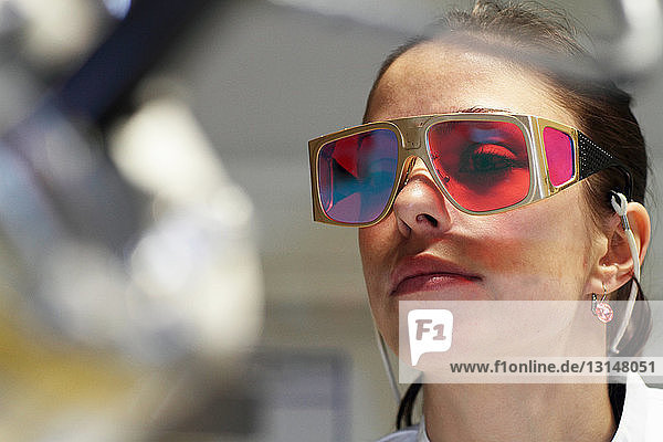 Close up of female scientist wearing red protective glasses