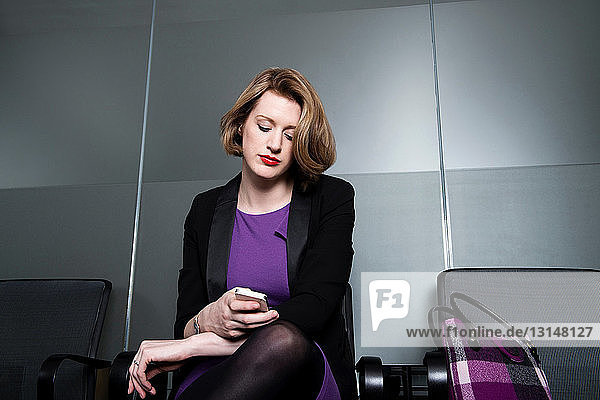 Business executive checking time or texting on smartphone Business executive checking time or texting on smartphone