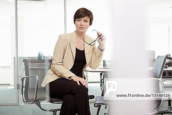 Businesswoman sitting in office chair at conference table  holding eyeglasses