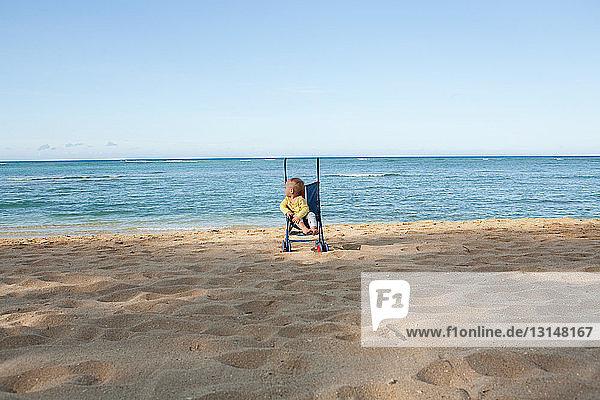 Toddler boy in pushchair on beach Toddler boy in pushchair on beach