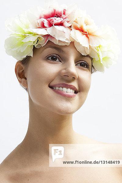 Studio portrait of beautiful young woman wearing flower headdress