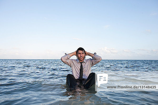 Businessman sitting in sea with head in hands