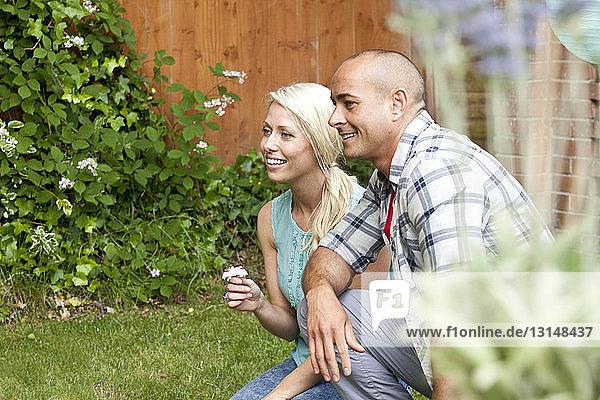 Couple crouching down in garden watching
