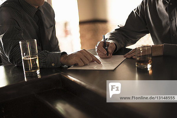 Partners signing business contract in a bar Partners signing business contract in a bar