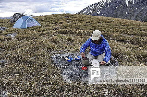Mid adult woman cooking food on camping stove  New Zealand