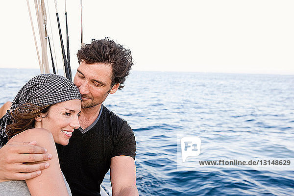 couple standing at rail of sailing boat