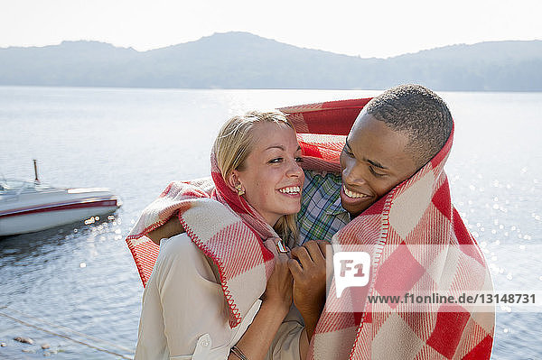 Young couple wrapped in blanket by lake  Hadley  New York  USA