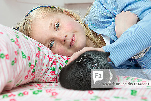 Portrait of young girl stroking pet guinea pig