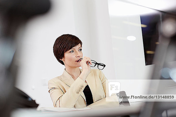 Businesswoman sitting in office chair holding eyeglasses to mouth