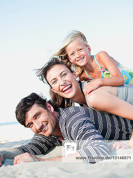 family lying in sand on beach smiling