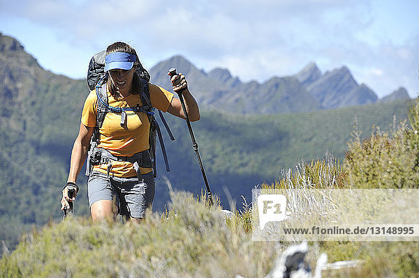 Mid adult woman hiking through Kahurangi National Park  New Zealand