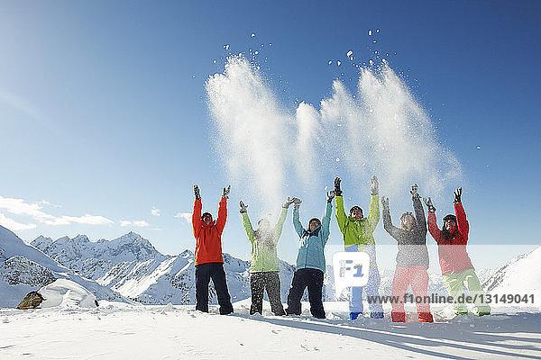 Friends throwing snow mid-air  Kuhtai  Austria