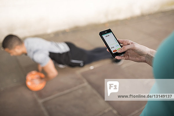 Over shoulder view of female trainer timing male runners push ups on smartphone
